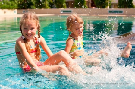Little girls in bathing suits kicking their feet in pool